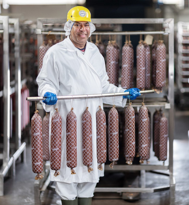 Employee holding rack of drying salami