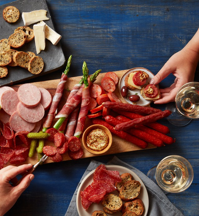 Charcuterie board covered with meat, cheese, crackers and spreads.