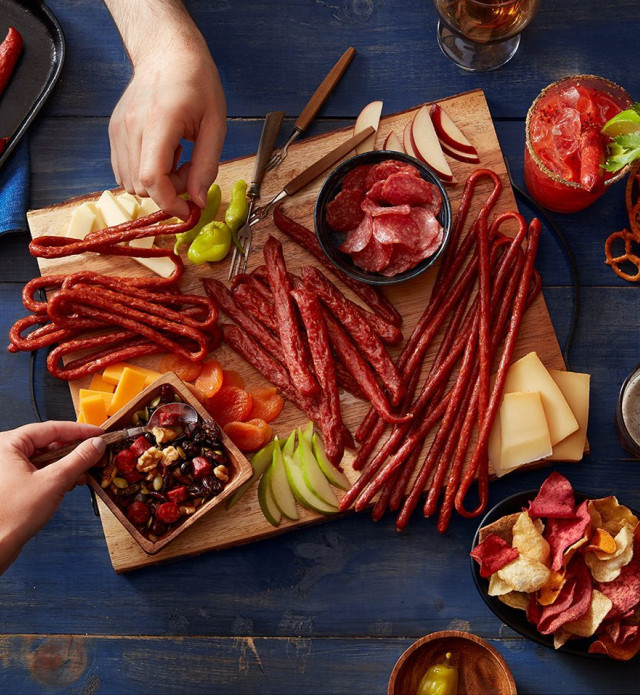 Hands reaching for meat snacks on a board