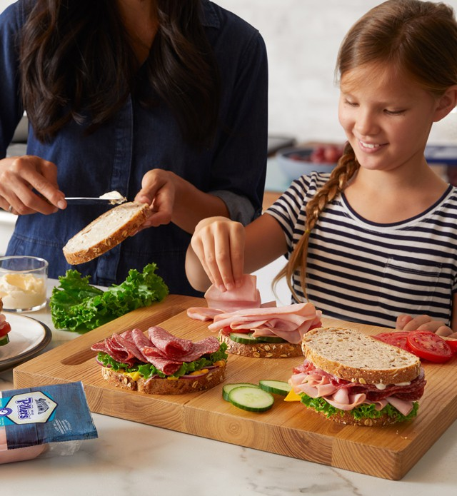 Mother and daughter making sandwiches on wooden cutting board.