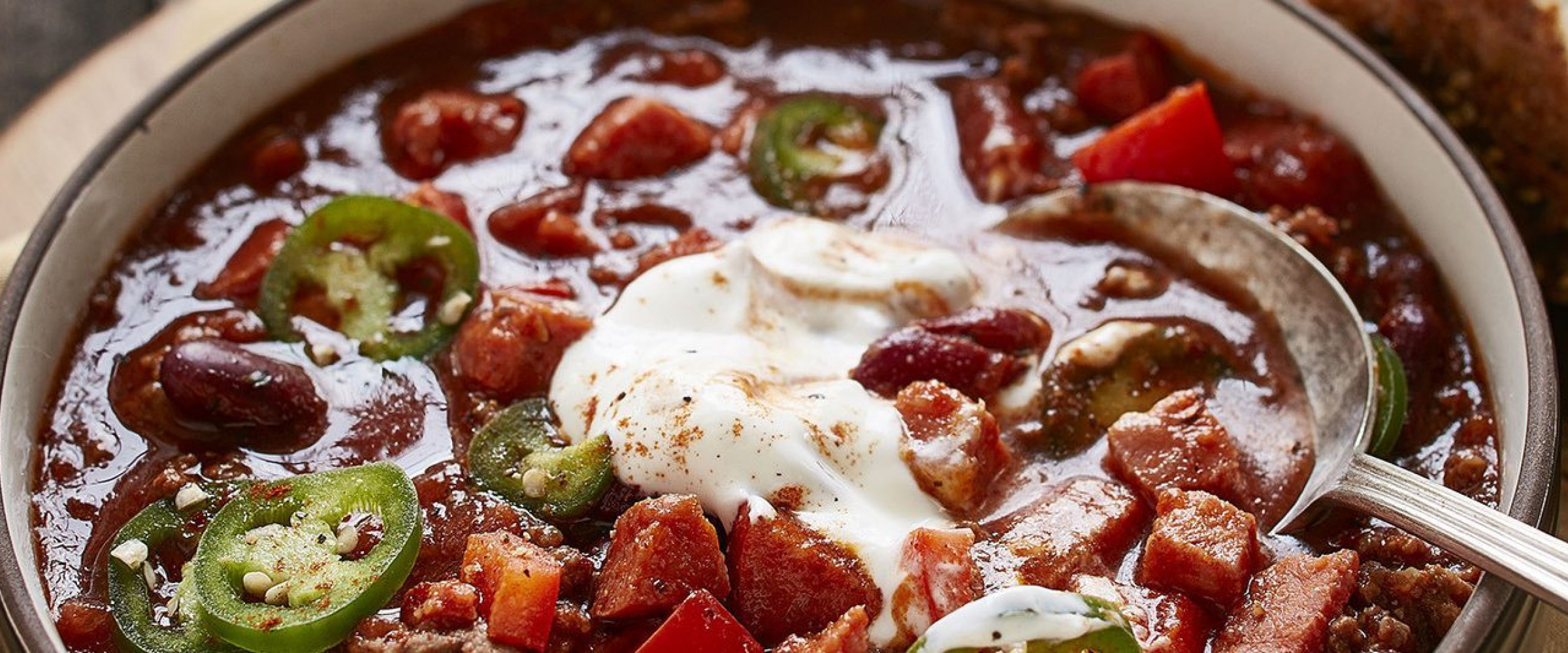 Bowl of chorizo and beef chili with sour cream on top