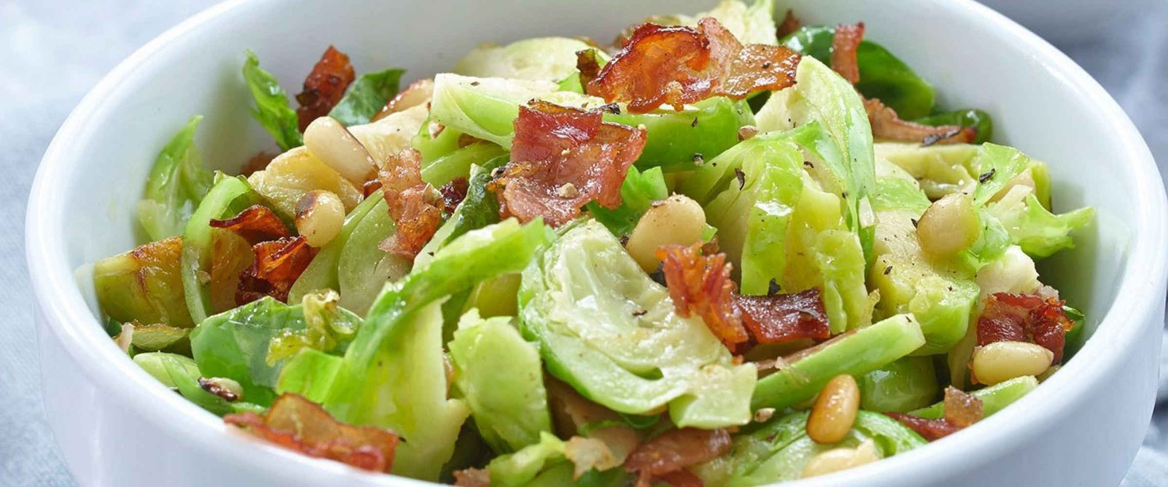 Brussel Sprouts shredded with Speck Prosciutto in a white bowl