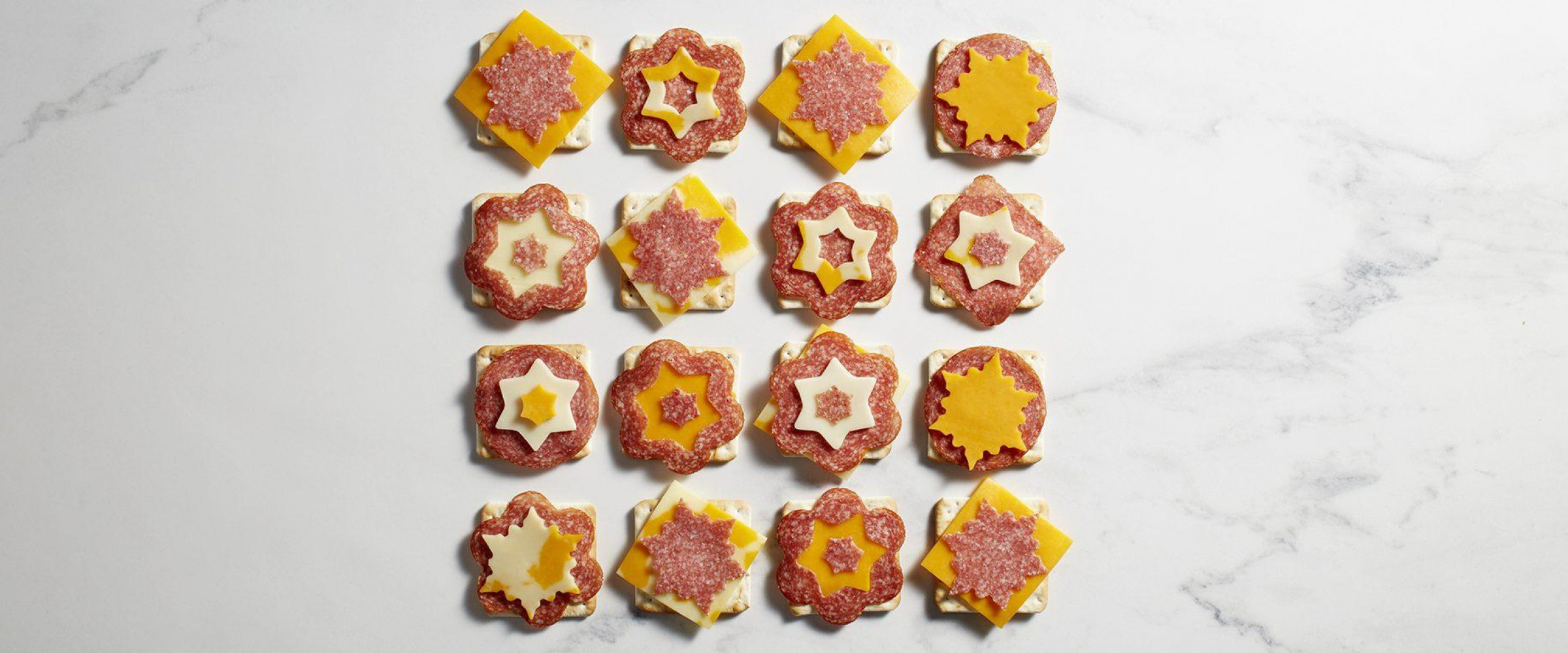 Salami and cheese and crackers cut into snowflake shapes