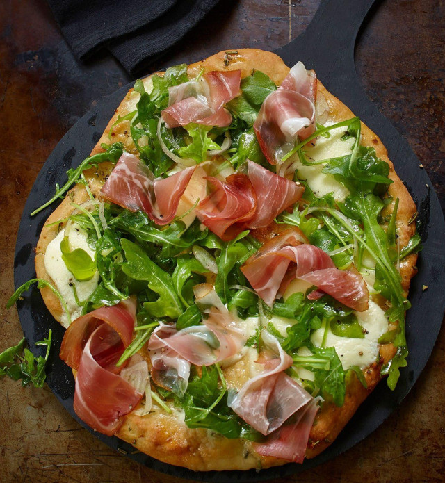 Pizza with arugula and speck prosciutto on a black pan