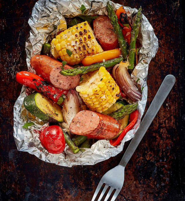 Grillwurst sausage and vegetables grilled in a foil packet