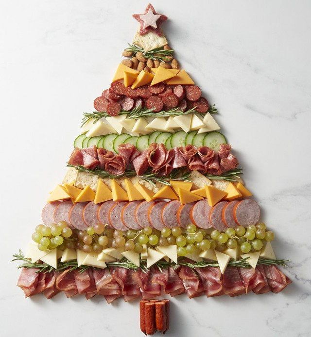 Charcuterie meats, cheeses, and fruits in the shape of a christmas tree